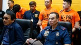 Gen. Guillermo Eleazar (right), then the Philippine National Capital region's police chief, and other police officials present three of 277 Chinese nationals arrested in a raid on an online investment scam syndicate during a news conference in Manila, Sept. 16, 2019.