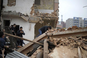 A resident reacts after failing to protect her home from a demolition crew in Guangdong province, March 21, 2012.