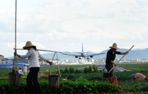 Farmers tend their crops near the airport in Kunming, in Yunnan province, June 27, 2012.