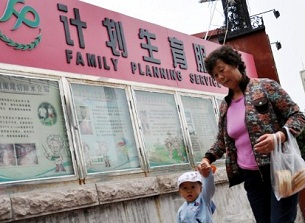 A woman walks with her grandson past a propaganda pavilion for family planning services and the one-child policy in Qingdao, Oct. 12, 2011.