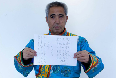 Hada displays a sign expressing support for herders in Mongolian and Chinese, Jan. 15, 2015.