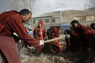In this undated photo, sent by a Yushu resident, monks assist rescue efforts at the quake site. Credit: Yushu resident