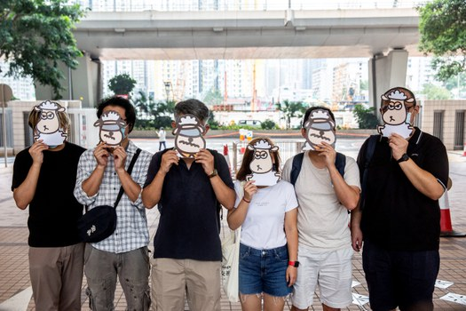 Supporters of a pro-democracy union pose with illustrations of sheep outside West Kowloon Court in Hong Kong, July 23, 2021. AFP