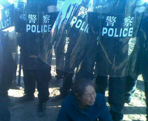 In a cellphone photo sent by an onlooker, a Mongolian lady sits in front of riot police, June 25, 2011.