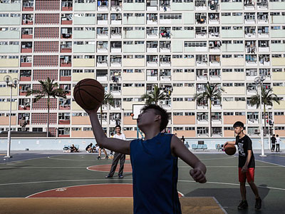 Youths play basketball in front of residential homes at a public housing estate in Hong Kong, April 1, 2017.