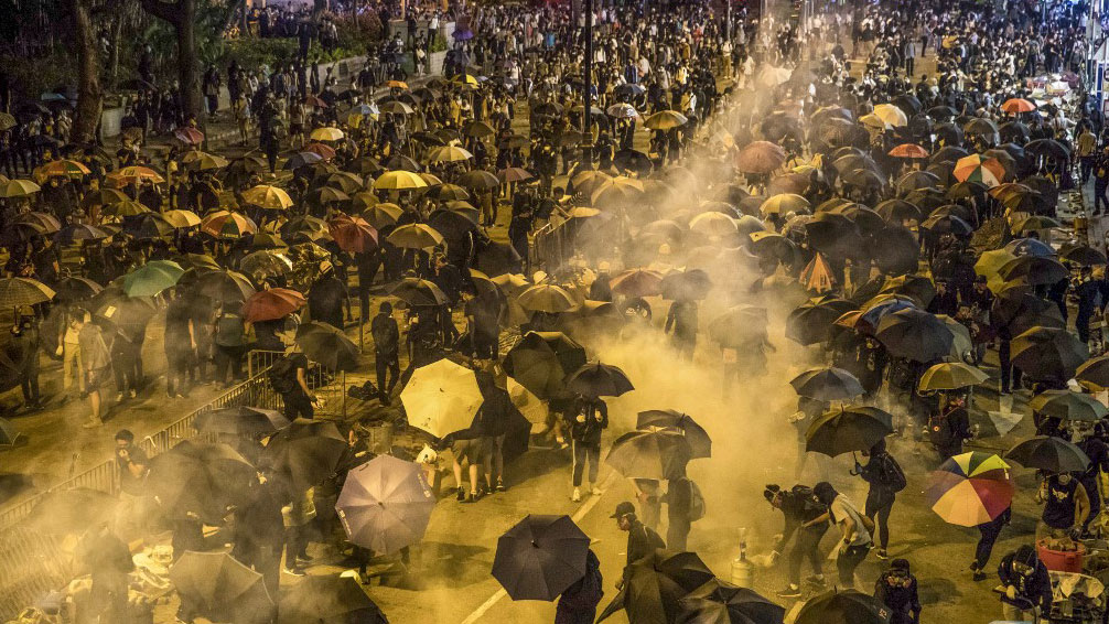 Hong Kong riot police fire tear gas at a fleeing protester in an undated photo. (Photo: AFP)