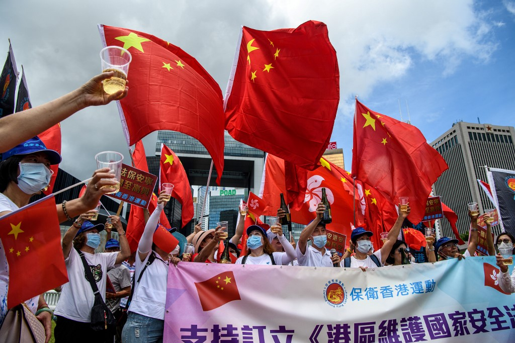 Pro-China supporters display Chinese and Hong Kong flags as they raise a toast with champagne during a rally near the government headquarters in Hong Kong, as China passed a sweeping national security law for the city, June 30, 2020.