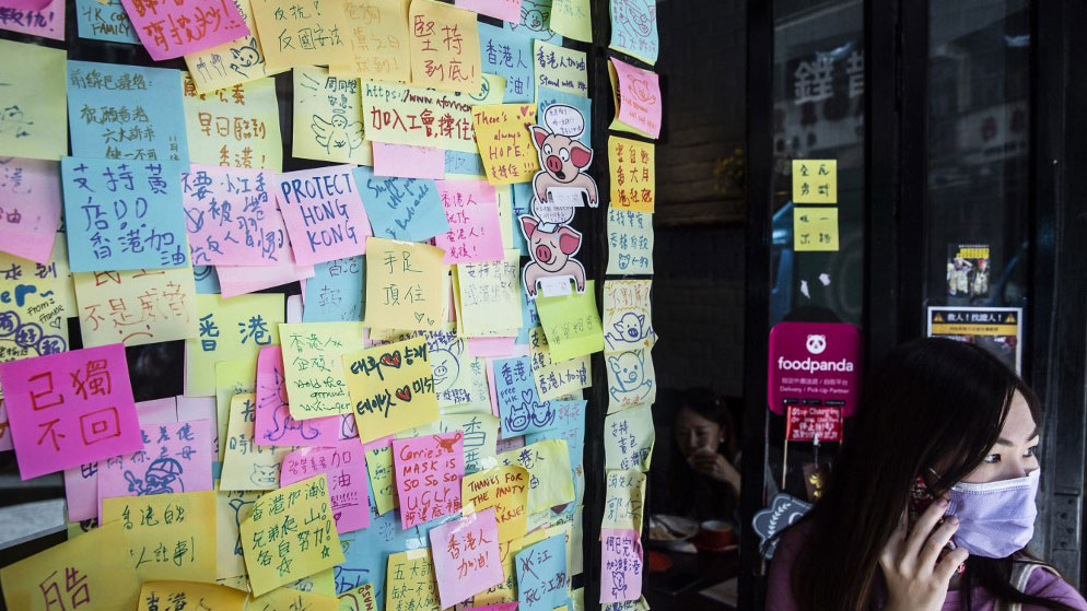 """A woman stands next to layers of notes on a """"Lennon Wall"""" with messages of support for the pro-democracy protests outside a restaurant in Hong Kong, July 3, 2020,"""