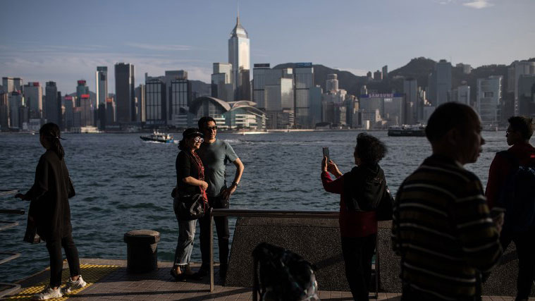 A mainland Chinese couple pose for photographs at a viewing deck before the skyline of Hong Kong island across the harbour, Feb. 16, 2019.   (AFP Photo)