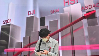 A pedestrian wearing a face mask, as a precautionary measure against the COVID-19 coronavirus, stands in front of an electronic stock market display in Hong Kong, in file photo.