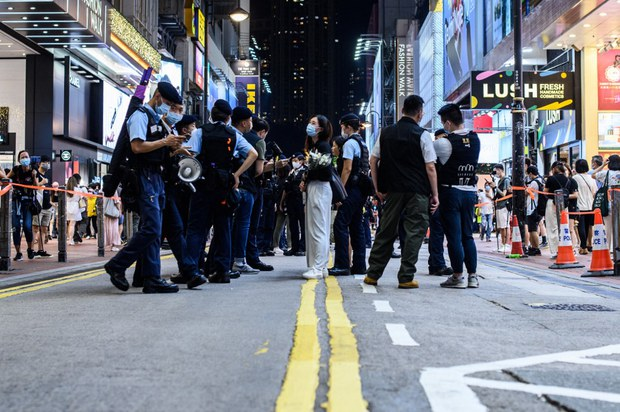 Police checking the belongings of people within a cordoned zone in Hong Kong's shopping district of Causeway Bay, near the site where 50-year-old Leung Kin-fai stabbed himself to death after knifing a policeman outside the Sogo department store, July 2, 2021.