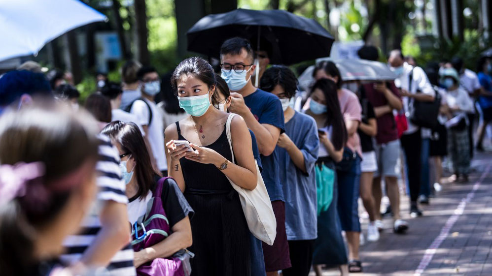 Voters line up to vote in primary elections as Hong Kong's pro-democracy parties held weekend primary polls to choose candidates for upcoming legislative elections, July 12, 2020.