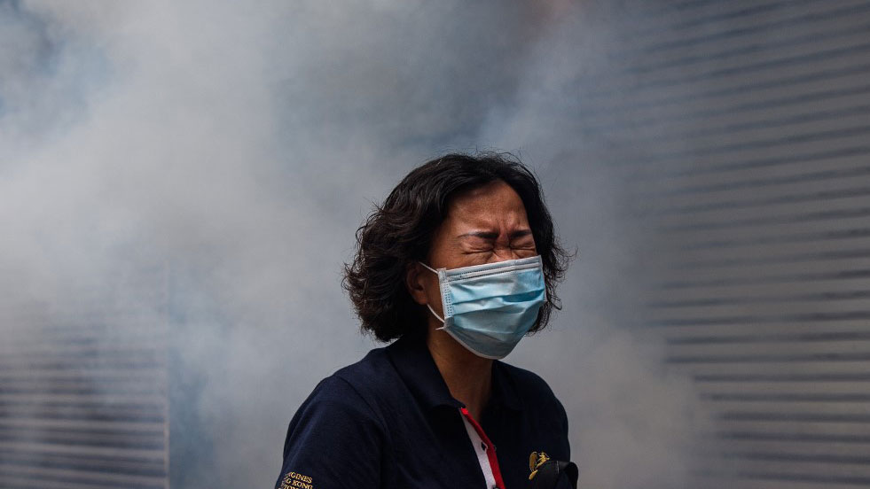 A woman reacts after riot police fired tear gas to disperse protesters taking part in a pro-democracy rally against a proposed new security law in Hong Kong, May 24, 2020.