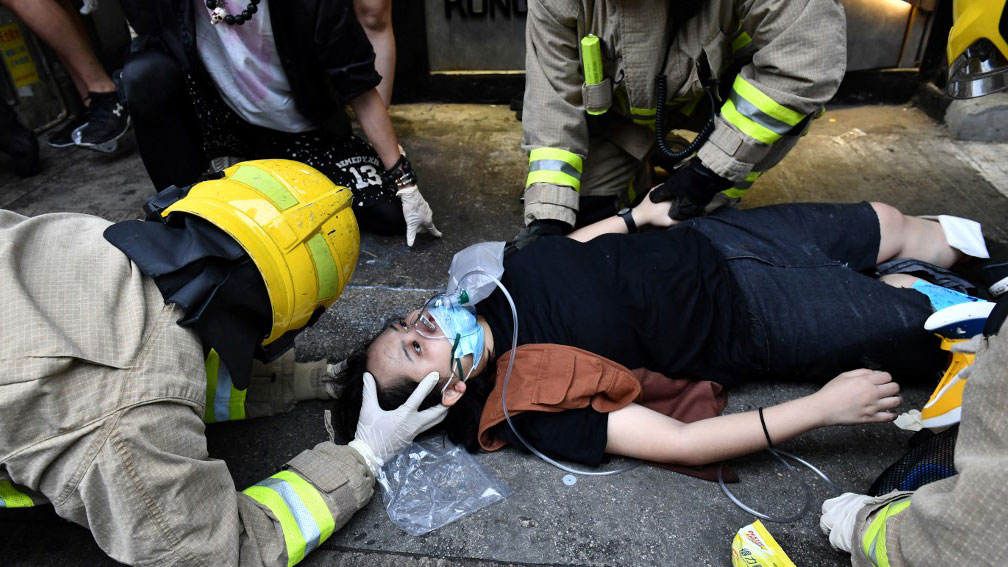 A protester receives medical assistance after a taxi hit two protesters during a demonstration in Hong Kong, October 6, 2019. (Photo: AFP)