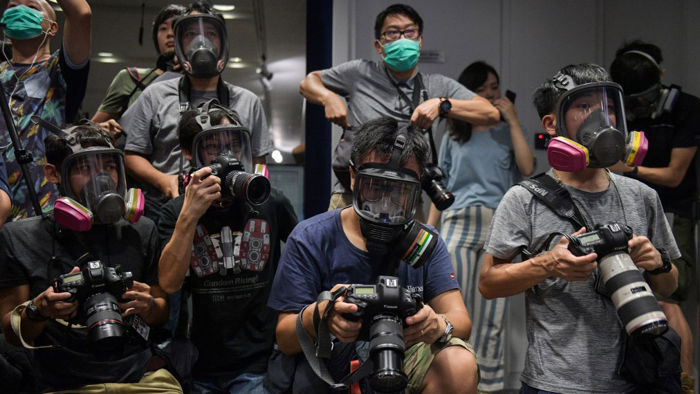 Photojournalists wearing protective masks attend a police press conference in Hong Kong Oct. 8, 2019.  (Photo: AFP)