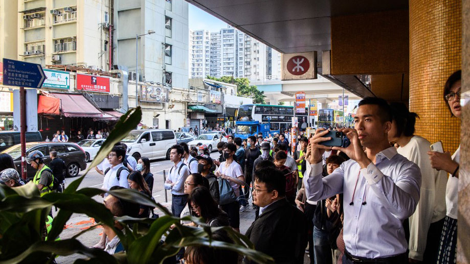 Bystanders stand behind a cordon set by police near the site where a pro-democracy protester was shot by a policeman in the Sai Wan Ho area of Hong Kong, Nov. 11, 2019. (Photo: AFP)