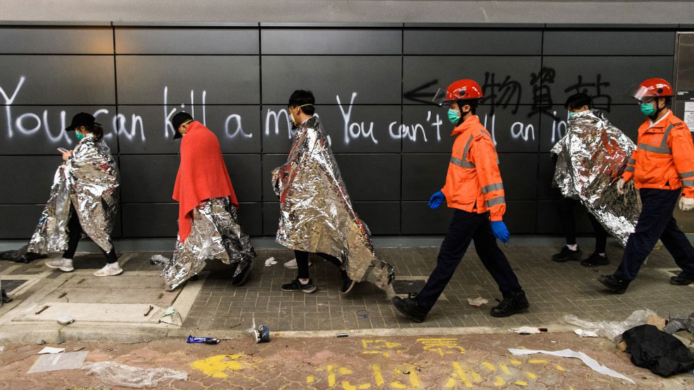 Anti-government protesters are taken by paramedics to ambulances from the campus of the Hong Kong Polytechnic University (PolyU) after being barricaded inside for days, in the Hung Hom district of Hong Kong,Nov. 20, 2019. (Photo: AFP)