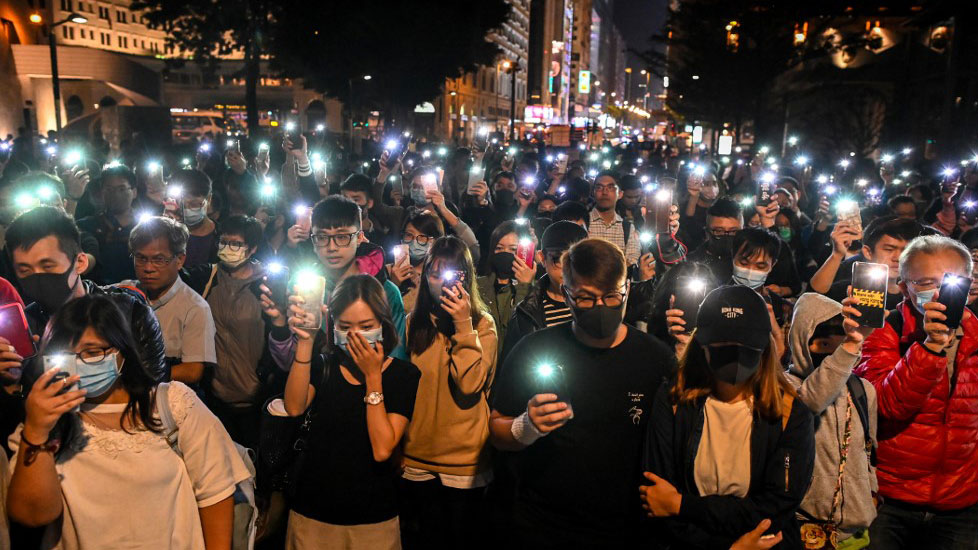 People hold their mobile phones as they gather to pray for the students who are barricaded inside Hong Kong Polytechnic University campus, Nov. 19, 2019.  (Photo: AFP)