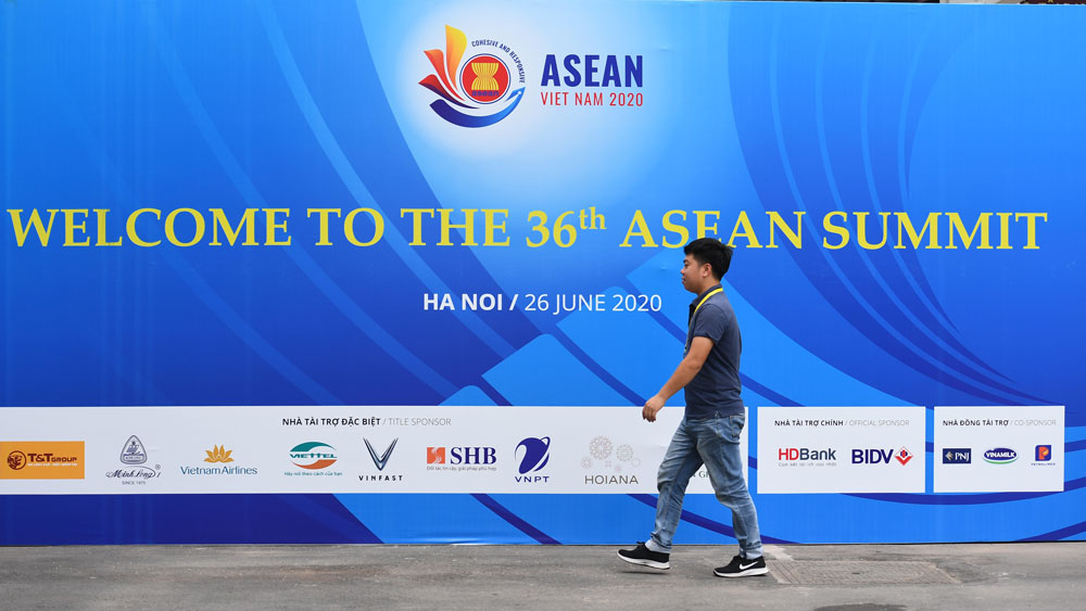 A man walks past a banner for the 36th ASEAN Summit at the International Convention Centre in Hanoi on June 25, 2020, a day before the summit is set to be held online due to the COVID-19 coronavirus pandemic.