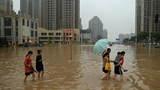 People wade across a flooded street in Zhengzhou, central China's Henan province, July 23, 2021.