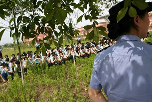 A file photo of a guard watching over women 're-education through labor' detainees during a drill in Chongqing.