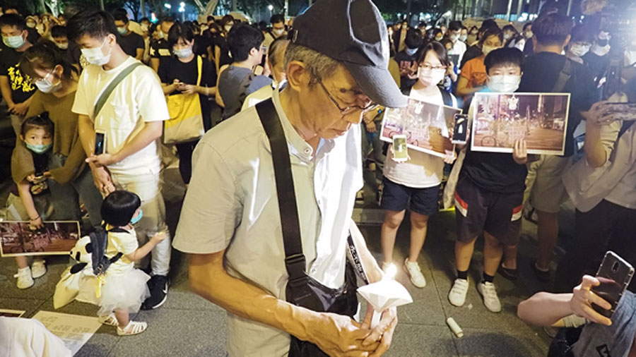 Former Hong Kong bookseller Lam Wing-kei, who has re-opened a bookstore in Taiwan after he and four colleagues were detained by Chinese police for books they sold, joins a candlelight vigil  in Taipei for the 31st anniversary of the 1989 Tiananmen massacre, June 4, 2020.