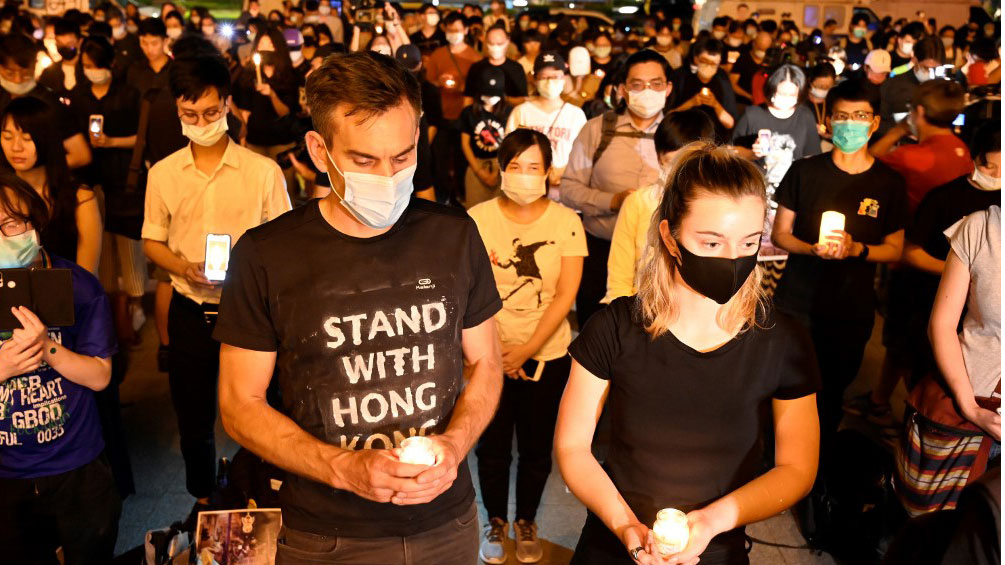People hold candles in front of the Chiang Kai-shek Memorial Hall, also known as Free Square, to mark the 31st anniversary of the 1989 Tiananmen Square crackdown in Taipei, June 4, 2020.