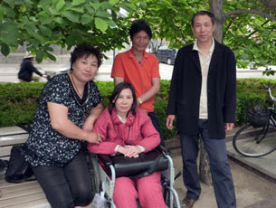 Ni Yulan (C) and her husband Dong Jiqin (3L) pose with friends near the Forbidden City in Beijing, May 27, 2010.
