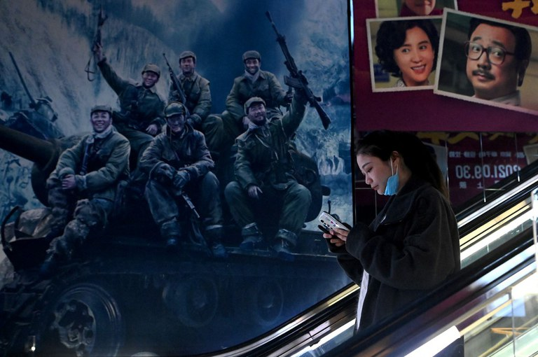 """A woman rides at an escalator past a movie promotion poster for """"The Battle of Lake Changjin,"""" a blockbuster film on the Koren War, at a mall in Beijing, Oct. 11, 2021. Credit: AFP"""
