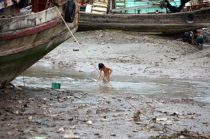 A Vietnamese boy washes up after working on a fishing boat, Nov. 29, 2009.