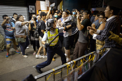 A policeman advances towards pro-democracy protesters as they clash on a street in the Mong Kok area of Hong Kong, Oct. 19, 2014. (Credit: AFP)