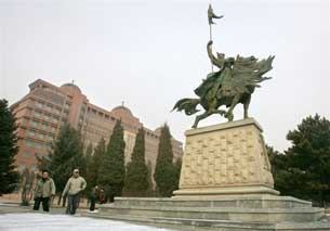 HOHHOT, China: Students approach a statue of Mongolian hero Genghis Khan on the Inner Mongolia University campus, 2006