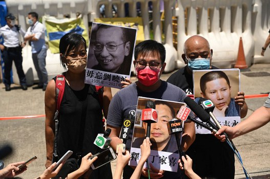Members of the pro-democracy group League of Social Democrats gather outside the Chinese Liaison Office in Hong Kong and hold up portraits of political prisoners, including one of Chinese Nobel Peace laureate Liu Xiaobo (pictured top L) on the fourth anniversary of his death, July 13, 2021. Credit: AFP