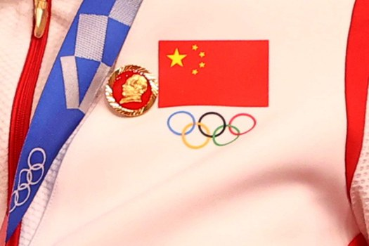 A badge of Mao Zedong, next to China's national flag and the Olympic symbol, on the uniform of a Chinese women's team member at the at the Women's Team Sprint medal ceremony in Shizuoka, Japan, Aug. 2, 2021. Credit: Reuters