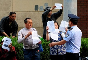 A policeman stops a group of petitioners from demonstrating outside a hospital in Beijing, May 7, 2012.