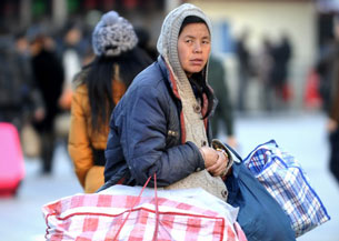 A Chinese woman prepares to take the train at the Beijing railway station ahead of the Lunar New Year, Feb. 4 , 2013.