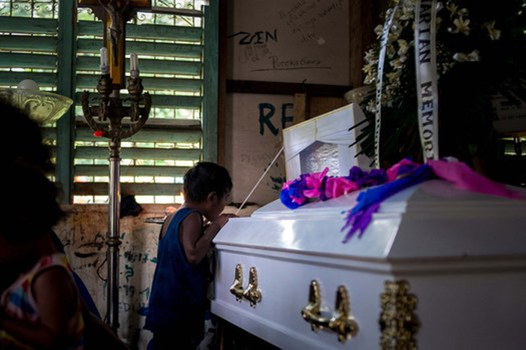"""Randy dela Cruz's son peeks into his father's coffin, March 16, 2021. Tribal communities have protested displacement due to the Kaliwa dam project, and have faced sometimes violent reprisals, including the killing of two Dumagat community members during an """"anti-communist"""" crackdown.  Credit: BenarNews"""