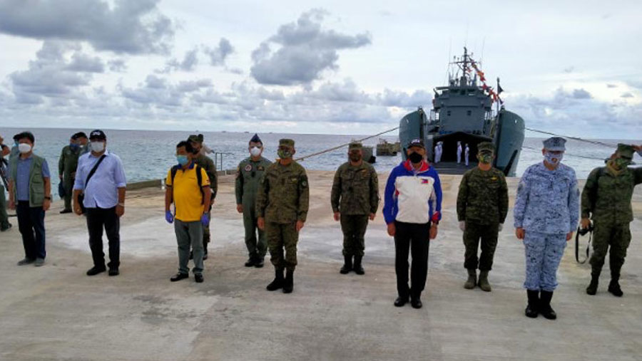 Philippine Defense Secretary Delfin Lorenzana (in white and blue jacket) joins defense officials as he inaugurates a beaching ramp on Pag-asa (Thitu) Island in the South China Sea, June 9, 2020.