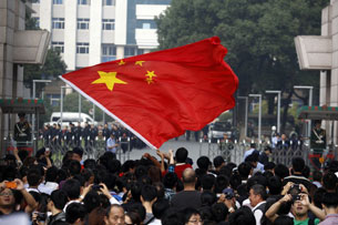 Chinese protesters wave the national flag outside government offices in Ningbo, Oct. 28, 2012.