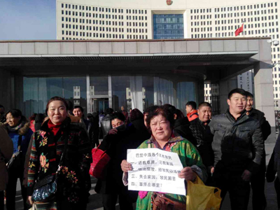 A protestor holds a sign outside a government building in Hohhot, Inner Mongolia, Jan. 26, 2015. (Photo courtesy of SMHRIC)