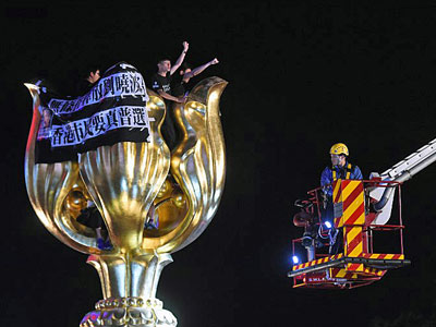 Pro-democracy demonstrators chant slogans as a fire engine crewmember attempts to remove them from the Golden Bauhinia statue in Hong Kong, June 28, 2017.