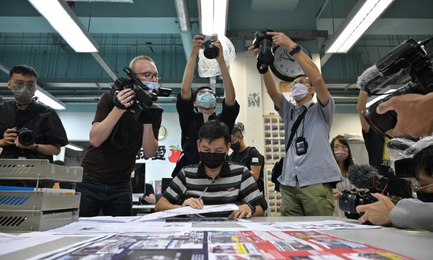 Members of the press take photos as executive editor-in-chief Lam Man Chung proofreads the final edition of Hong Kong's Apple Daily newspaper, June 23, 2021.