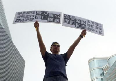 A pro-democracy protester holds anti-government placards demanding justice for the people in Hong Kong, Oct. 2, 2014. Credit: RFA