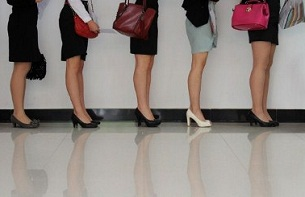 Women line up to interview for positions as flight attendants at a job fair in Wuhan, April 18, 2012.