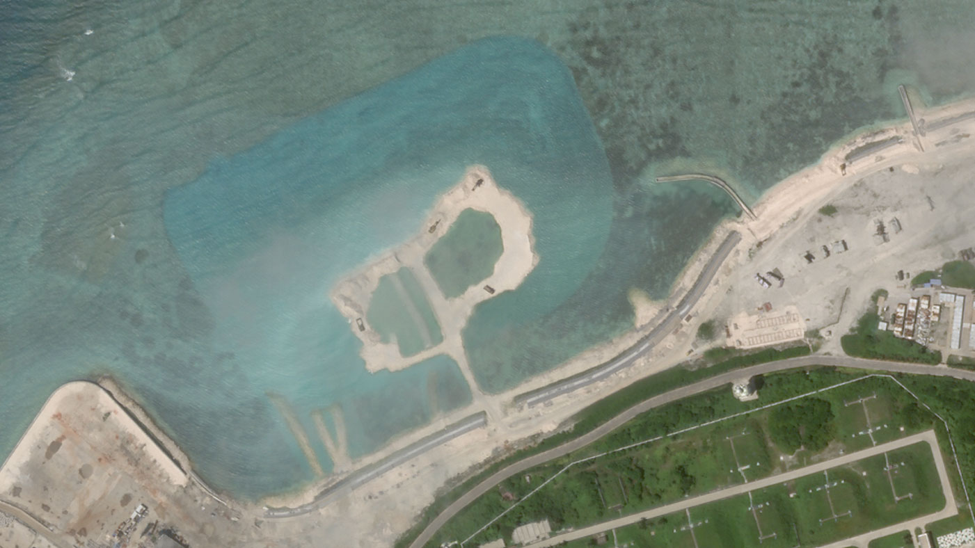 Satellite imagery dated Oct. 5 shows a patch of reef in Woody Island's northwest that has been dredged up, as indicated by the blue color of the water around it.