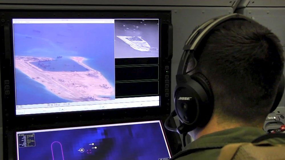 A U.S. Navy crewman aboard a P-8A Poseidon surveillance aircraft views a computer screen showing Chinese construction on the reclaimed land of Fiery Cross Reef in a still image from video provided by the United States Navy May 21, 2015.
