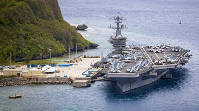 """The aircraft carrier USS Theodore Roosevelt, leader of a carrier strike group that entered the South China Sea on a """"freedom of navigation"""" exercise on Jan. 23, 2021, seen moored pier side in Guam in a May 2020 U.S. Navy photo."""