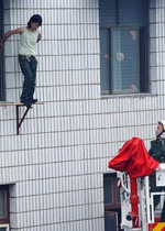 A Chinese woman standing on a tower block is approached by a rescue worker. Photo: RFA