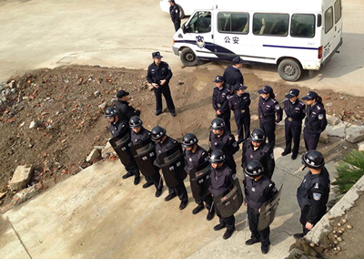 Police surround the building where the activists are staying in Suzhou, April 29, 2015.