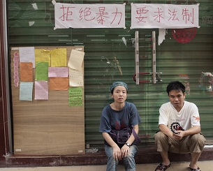 Xiaoxiaocao Workers' Home staff sit outside their shuttered office, Aug. 30, 2012.